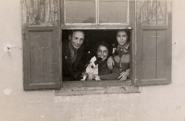 German Jewish refugees, the Gerechter family and a dog looks out the window of their refuge in Albania.